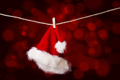 Red santa hat hanging on defocused lights Stock Images