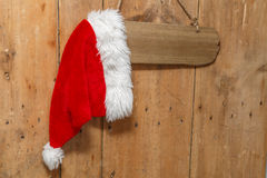 Red Santa hat hanging on a sign on an old front door. Red Santa hat hanging on a blank sign on an old wooden front door Royalty Free Stock Photography