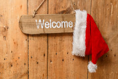 Red Santa hat hanging on a welcome sign on an old front door. Red Santa hat hanging on a welcome sign on an old light colcoured wooden front door Royalty Free Stock Photos