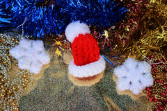 Red Santa hat in a miniature close up on  shiny gold background with festive decorations Stock Photos