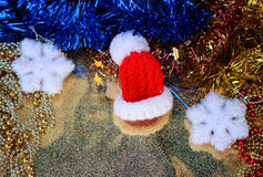 Red Santa hat in a miniature close up on  shiny gold background with festive decorations Royalty Free Stock Image