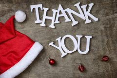 Red santa hat on textured wooden background and Thank you wooden Royalty Free Stock Images