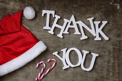 Red santa hat on textured wooden background and Thank you wooden Stock Photography
