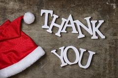 Red santa hat on textured wooden background and Thank you wooden Stock Image