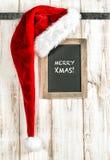 Red Santa hat and vintage chalkboard. Retro christmas decoration Stock Photo