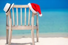 Red santa hat and white straw hat on beach chair Stock Photos
