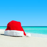 Red santa hat on white tropical beach sand - Christmas or New Ye Royalty Free Stock Photography