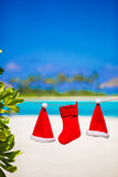 Red Santa hats and Christmas stocking hanging on Royalty Free Stock Images