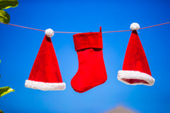 Red Santa hats and Christmas stocking hanging on tropical beach between palm trees Stock Image