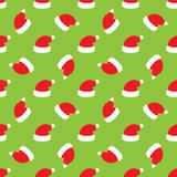 Red Santa hats on green background. Vector illustration Royalty Free Stock Images