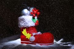 Red Santa`s boot with christmas gifts on dark background. Happy holidays composition. Red Santa`s boot with christmas gifts on dark background. Happy holidays stock images