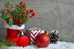 Red Santa`s boot with fir tree branch,decorative holly berry leaves,candy cane,gift,pine cone and Christmas ball. Royalty Free Stock Photo