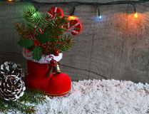 Red Santa`s boot with fir tree branch,decorative holly berry leaves,candy cane,pine cones ans garland.Christmas decoration. Royalty Free Stock Image