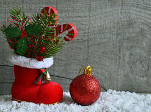 Red Santa`s boot with fir tree branch,decorative holly berry leaves,candy cane and red Christmas ball. Stock Photo