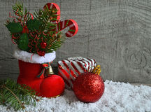 Red Santa`s boot with fir tree branch,decorative holly berry leaves,candy cane and red Christmas ball. Royalty Free Stock Photo