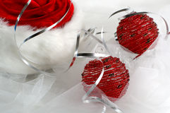 Red Santa's hat with christmas ornaments. Partial of red spiral Santa's hat with christmas red ornaments, silver ribbon and white mesh Royalty Free Stock Photography