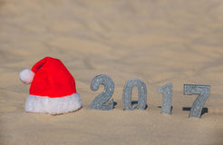 Red Santa's hat lies on the beach, next to the sand are the numbers of the new year with silver sequins. New Year's holidays in the ocean or sea Stock Images