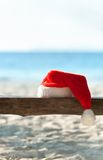 Red Santa's hat on wooden bench on the beach Royalty Free Stock Photography
