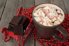 Red Santa's sleigh with chocolate, hot cocoa with marshmallows, Christmas decorations. Christmas miracle soon Stock Photo
