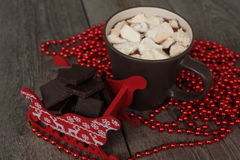 Red Santa's sleigh with chocolate, hot cocoa with marshmallows, Christmas decorations. Christmas miracle soon Royalty Free Stock Images