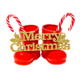 Red Santa shoes with candy sticks and golden Merry Christmas write, close up, isolated. Stock Photo