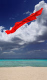 Red sarong. A red sarong floating in mid-air above a white sand beach with sea and sky background Royalty Free Stock Images