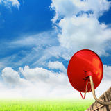 Red satellite dish with blue sky background. Stock Photos