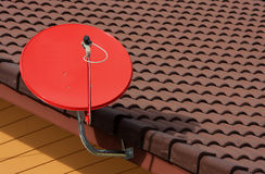 Red satellite on roof on blue sky. Royalty Free Stock Photo