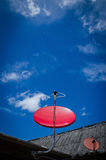 Red Satellite TV Receiver Dish on the Old  Roof Stock Photography