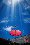 Red Satellite TV Receiver Dish on the Old  Roof Royalty Free Stock Image