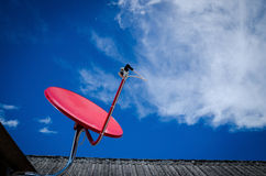 Red Satellite TV Receiver Dish on the Old  Roof Royalty Free Stock Photo