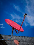 Red Satellite TV Receiver Dish on the Old  Roof Stock Image
