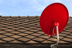 Red Satellite TV Receiver Dish on the Old Tiles Roof. Closeup Royalty Free Stock Photography