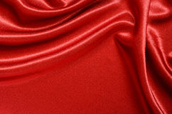 Red satin. Draped with soft folds Stock Photos