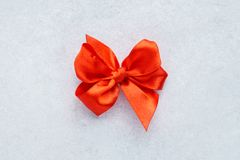 Red satin gift bow on light gray background. Greeting card. stock image