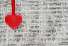 Red satin heart on a string rests on a background Stock Photos