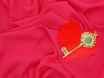 Red satin material with key to heart shape love concept Royalty Free Stock Images