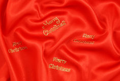 Red Satin with Merry Christmas. Crumpled red satin with Merry Christmas motifs Stock Photography