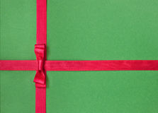Red satin ribbon with bow. On green background Royalty Free Stock Image