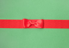 Red satin ribbon with bow. On green background Stock Photo