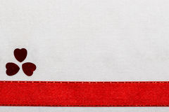Red satin ribbon hearts on white cloth. Royalty Free Stock Image