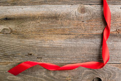 Red satin ribbon on reclaimed wood, valentines day background Stock Photo