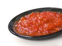 Red sauce on the black saucer isolated over white Stock Photos
