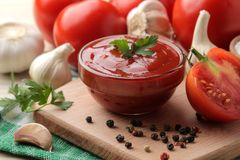 Red sauce in a bowl closeup with fresh ingredients, tomatoes, garlic and spices on a natural wooden table. stock photo