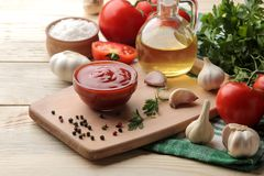 Red sauce in a bowl with fresh ingredients, tomatoes, garli c and oil and spices on a natural wooden table. stock photography