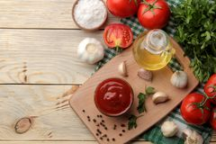 Red sauce in a bowl with fresh ingredients, tomatoes, garlic and oil and spices on a natural wooden table. view from above stock images