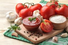 Red sauce in a bowl with fresh ingredients, tomatoes, garlic and spices on a natural wooden table. royalty free stock image