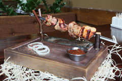 Red sauce, onion and shish kebab on a plate. Shish kebab on a skewer of pork Stock Photography