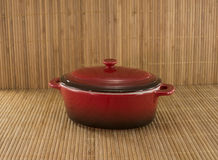 Red saucepan on bamboo Stock Photo