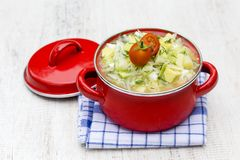 Red saucepan with okroshka - traditional summer soup in Ukraine, Belarus and Russia. Close up Stock Photos